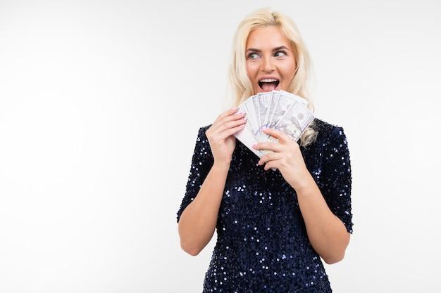 Portret pomyślna kobieta trzyma wiązkę pieniądze w jej rękach na białym tle z kopii przestrzenią w sukni