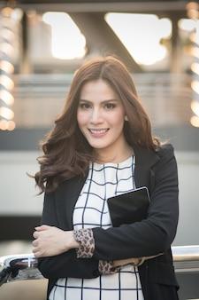 Portret pomyślna mądrze biznesowej kobiety przyglądający i uśmiechnięty mienie pastylki komputer