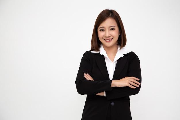 Portret pomyślne biznesowe azjatykcie kobiety w czarnym kostiumu z rękami krzyżować i uśmiech odizolowywający, młody bizneswomanu ono uśmiecha się
