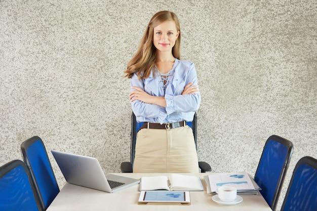 Portret pomyślnego bizneswomanu pozycja przy biurkiem z rękami składać