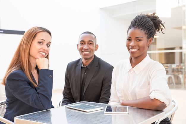 Portret pomyślni biznesmeni siedzi przy kawiarnia stołem