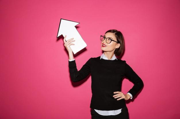 Portret pomyślny młody bizneswoman wskazuje w górę strzała
