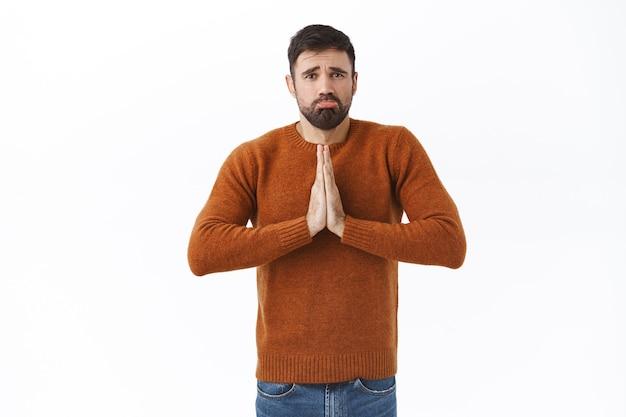 Portret ponurego, jęczącego młodego mężczyzny, który utknął w trudnej sytuacji, potrzebuje pożyczyć pieniądze, złożyć ręce do modlitwy, szlochać i marszczyć brwi, błagać o przysługę, potrzebować pomocy, stać białą ścianą