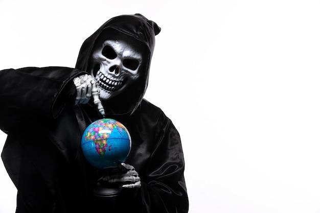 Portret ponurego żniwiarza w czarnych ubraniach z małą kulą ziemską na białym