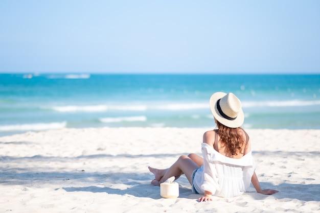 Portret portret pięknej kobiety azjatyckie cieszyć siedzieć i pić sok kokosowy na plaży