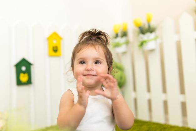 Portret portret słodkie dziewczynki bawiące się w swoim przytulnym pokoju dla dzieci.