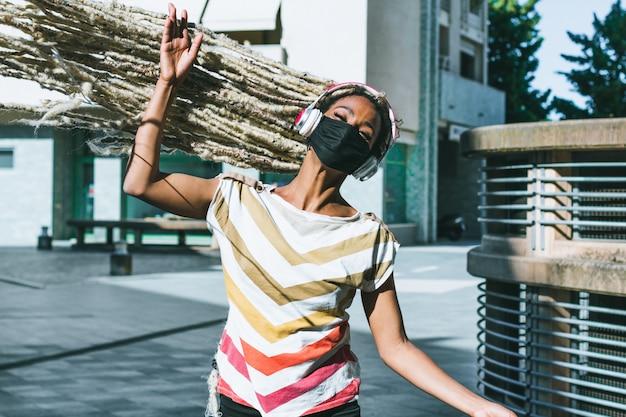Portret poruszającej blond dreadlocks afrykańskiej dziewczyny włosiana słuchająca muzyka podczas gdy będący ubranym twarzy ochronną maskę