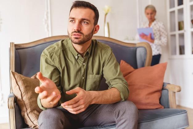 Portret posępnego młodzieńca rozmawiającego podczas sesji terapeutycznej w swoim gabinecie psychologów