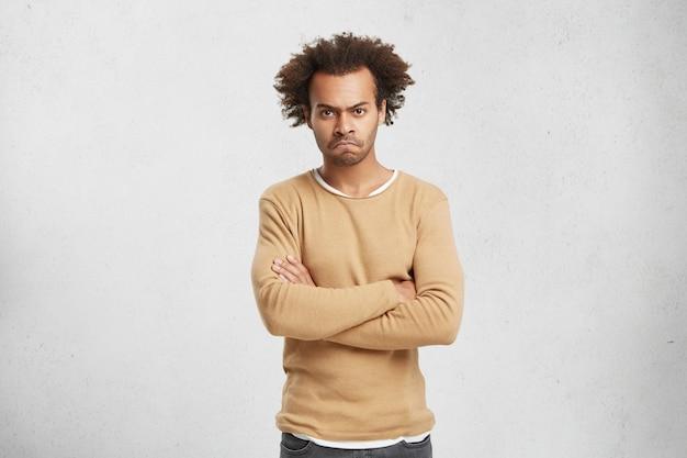 Portret posępnego, zrzędliwego mężczyzny z włosami i kręconymi włosami, z założonymi rękami