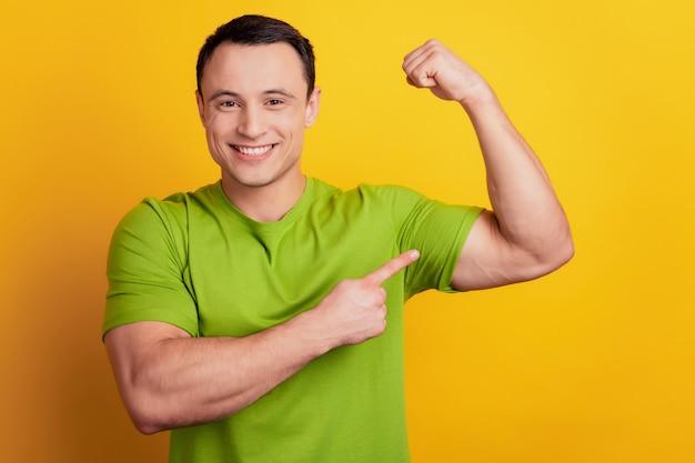 Portret potężnego faceta bezpośredniej porady sportowej bicepsów na żółtym tle