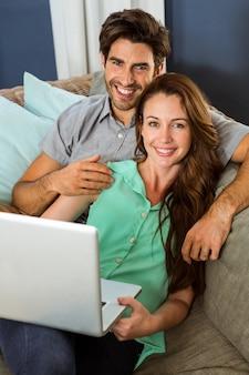 Portret potomstwa dobiera się obsiadanie na kanapie i używać laptopie