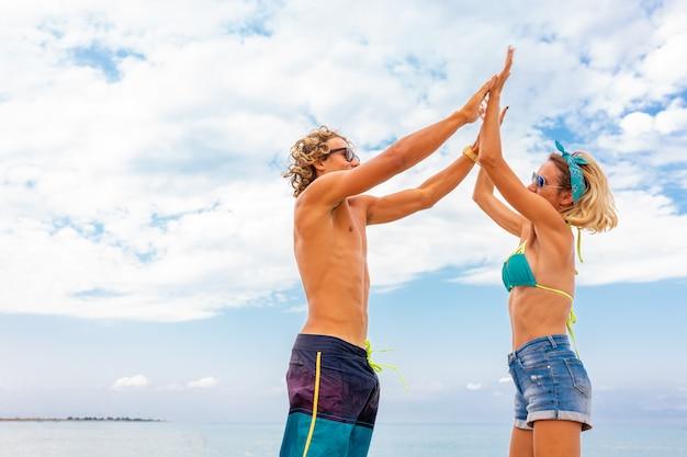 Portret potomstwa dobiera się w miłości obejmuje przy plażą i cieszy się czas jest wpólnie. młoda para zabawy na piaszczystym wybrzeżu