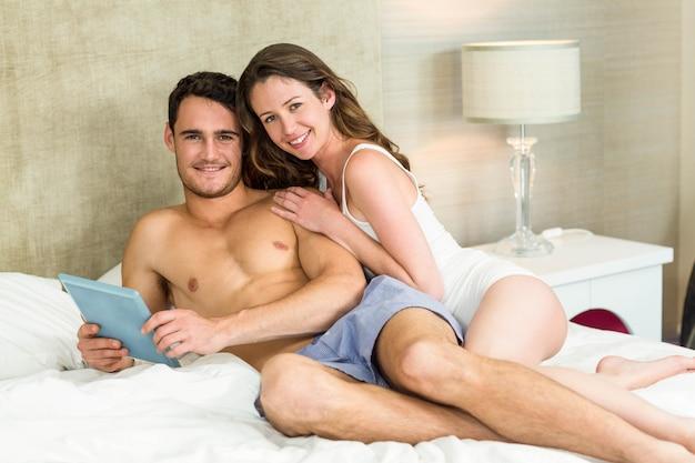 Portret potomstwo para używa cyfrową pastylkę i relaksujący na łóżku