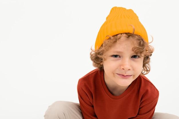 Portret powabna chłopiec z kędzierzawym włosy, żółci kapeluszowi uśmiechy odizolowywający na białym tle