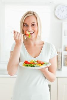 Portret powabna kobieta cieszy się mieszanej sałatki