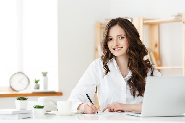 Portret powabny bizneswomanu obsiadanie przy jej pisaniem i miejscem pracy