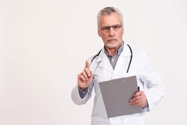 Portret poważna lekarka w białej todze z stetoskopem
