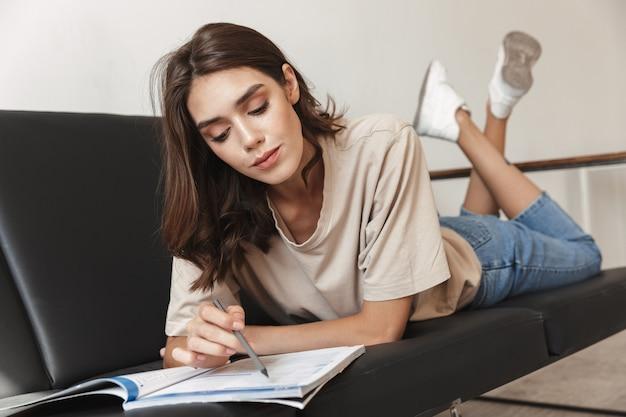 Portret poważne młoda ładna kobieta siedzieć w domu na kanapie w domu na odrabianiu lekcji, studiując pisanie czegoś w zeszycie.