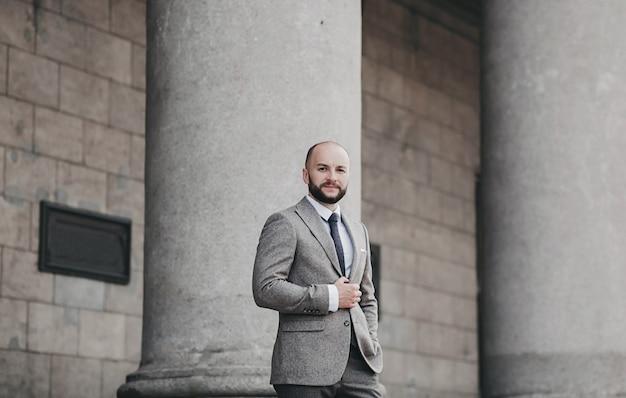 Portret poważne modne przystojny mężczyzna w garniturze pozowanie w mieście