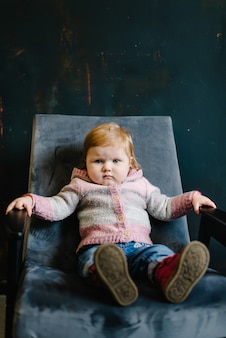 Portret poważne rude włosy dziewczynka siedzi w starym fotelu na tle starego muru. maluch w studio.