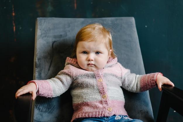 Portret poważne rude włosy dziewczynka siedzi w starym fotelu na tle starego muru