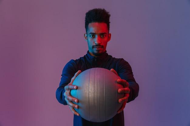 Portret poważnego afroamerykanina w sportowej pozowanie z fitballem na białym tle nad fioletową ścianą