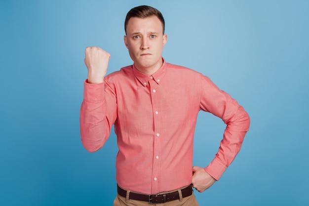 Portret poważnego agresywnego brutalnego faceta podnosi pięść gniewną twarz aparat na niebieskim tle