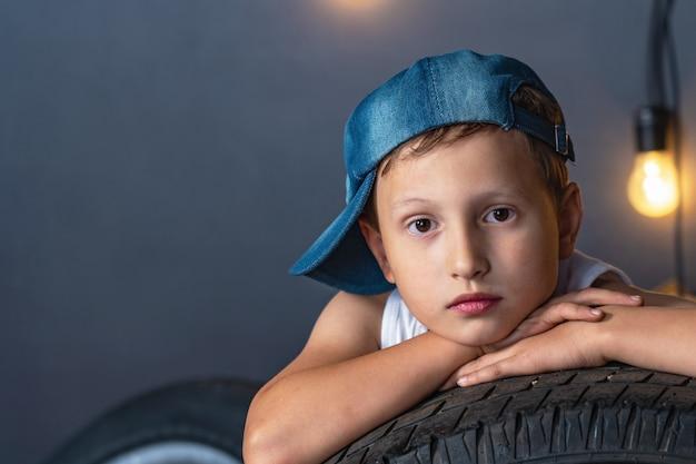 Portret poważnego chłopca w wieku 7 lat, ileaning na oponie samochodu w garażu