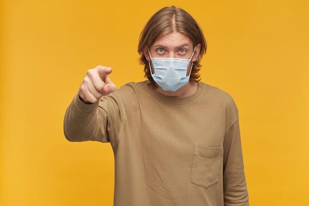 Portret poważnego, dorosłego mężczyzny o blond włosach i brodzie. noszenie beżowego swetra i medycznej maski ochronnej. wskazuje na ciebie palcem. pojedynczo na żółtej ścianie