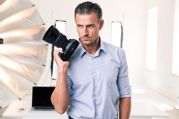 Portret poważnego fotografa trzymającego aparat w studiu