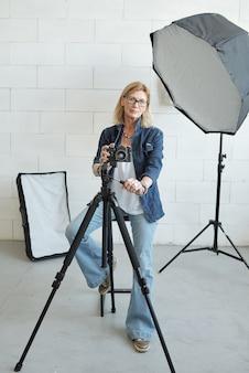 Portret poważnego fotografa w okularach, dostosowując aparat na statywie podczas pracy w studio fotograficznym