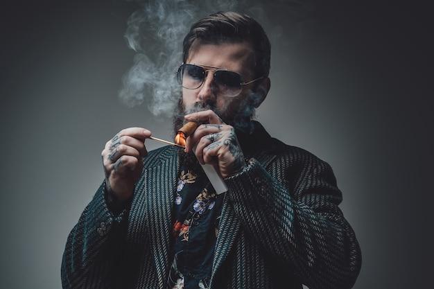 Portret poważnego i przystojnego mężczyzny ze stylową fryzurą pozowanie na szarym tle. wytatuowany mężczyzna palący cygaro.