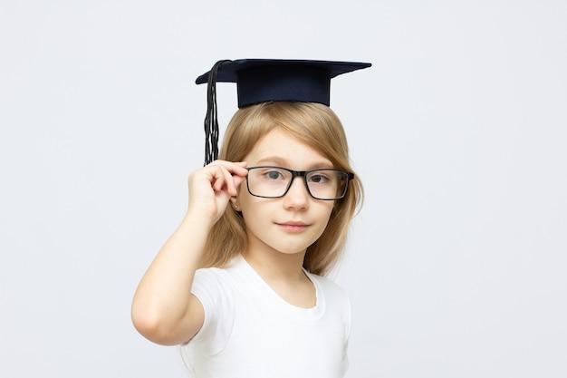Portret poważnego inteligentnego chłopca na sobie garnitur i akademicki kapelusz i okulary. koncepcja edukacyjna. pojedynczo na białym.