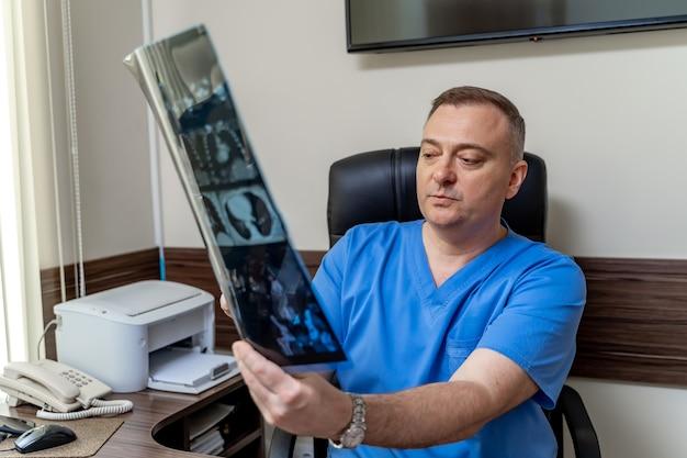 Portret poważnego lekarza. mężczyzna specjalista medyczny. chirurg lub radiolog na tle sali medycznej.