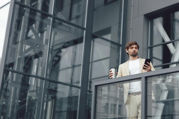 Portret poważnego mężczyzny ubranego w modny garnitur o rozmowie wideo na smartfonie, stojąc na zewnątrz przy filiżance kawy
