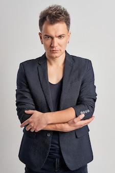 Portret poważnego mężczyzny w dżinsach, koszulce i dopasowanej kurtce