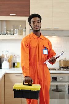 Portret poważnego młodego afroamerykańskiego brodatego hydraulika w pomarańczowej odzieży roboczej, trzymającego schowek i skrzynkę narzędziową, stojąc w kuchni