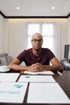 Portret poważnego młodego biznesmena siedzącego przy stole pokrytym sprawozdań finansowych, wykresów i diagramów