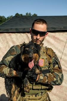Portret poważnego młodego brodatego żołnierza w okularach przeciwsłonecznych i stroju kamuflażowym, trzymającego słodkiego psa w obozie wojskowym