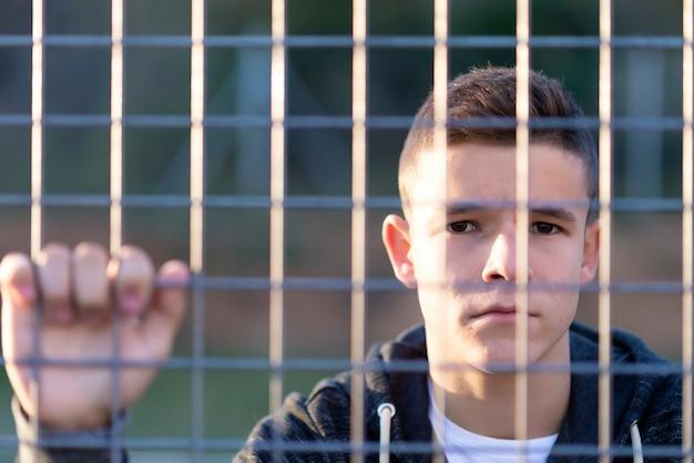 Portret poważnego młodego mężczyzny pochylony za płotem z łańcucha, patrząc na kamery