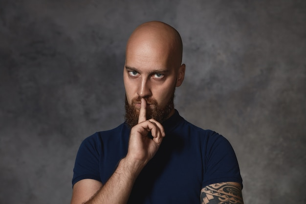 Portret poważnego, młodego, wytatuowanego mężczyzny z ogoloną głową i krzaczastą brodą o surowym, groźnym wyrazie twarzy, trzymającego palec na ustach, mówiącego, żeby trzymać usta na kłódkę