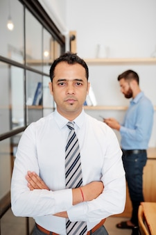 Portret poważnego pewnego siebie indyjskiego biznesmena krzyżującego ramiona i patrzącego na kamerę, gdy stoi w biurze