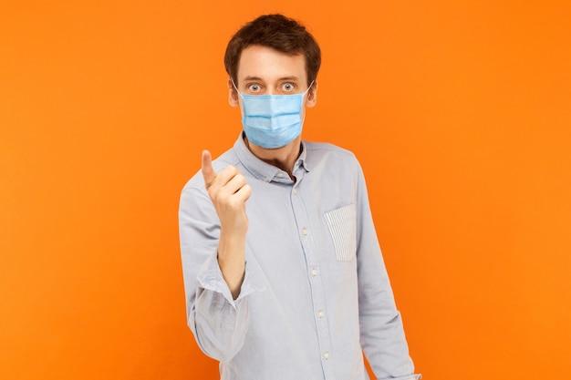Portret poważnego pracownika młodego człowieka z chirurgiczną maską medyczną stojącą i ostrzeżeniem w aparacie. koncepcja opieki zdrowotnej i medycyny. kryty studio strzał na białym tle na pomarańczowym tle.