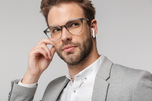 Portret poważnego przystojnego mężczyzny w okularach za pomocą słuchawek izolowanych na białej ścianie