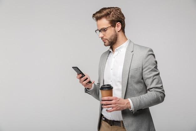 Portret poważnego przystojnego mężczyzny w okularach za pomocą telefonu komórkowego i trzymającego papierowy kubek na białym tle nad białą ścianą