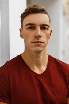 Portret poważnego przystojnego młodzieńca w modnej czerwonej koszulce ze stylową fryzurą w pobliżu zabytkowego białego budynku.