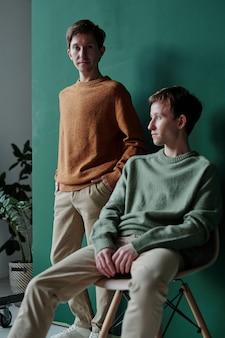Portret poważnego przystojnego młodzieńca w swetrze, trzymającego się za ręce w kieszeniach i jego brata animowanego, siedzącego na krześle i odwracającego wzrok