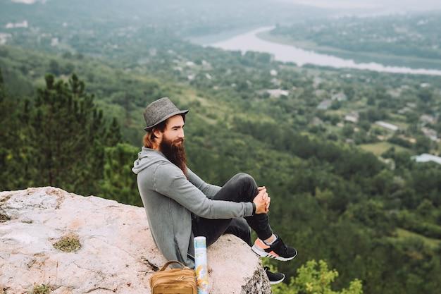 Portret poważnego stylowego brodatego hipster siedzącego na skale na górze na tle epickiego krajobrazu
