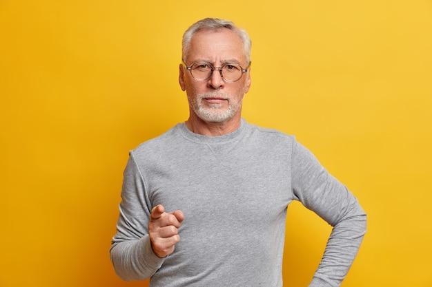 Portret poważnego, surowego brodatego mężczyzny ostrzega palcem, który udziela mądrej rady, nosi szary sweter z długimi rękawami, wygląda pewnie z przodu odizolowany na żółtej ścianie