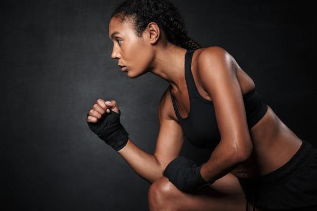 Portret poważnej afroamerykańskiej kobiety w odzieży sportowej i owija się dłonią, biegnąc na czarnym tle